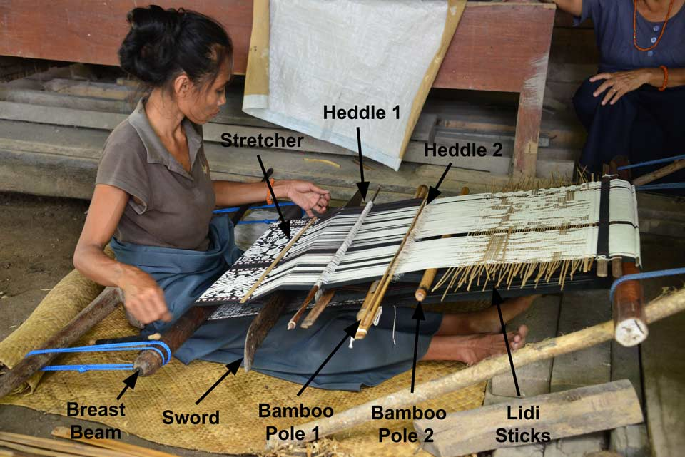Description: A young weaver at Pau working on the lower panel of a lau pahikung