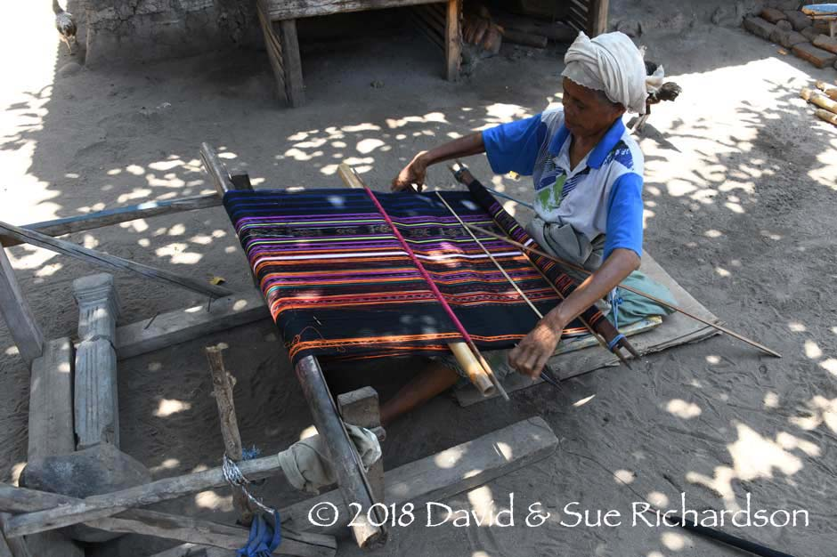Description: Weaving a sarong with chemical stripes and naturally dyed bands of ikat
